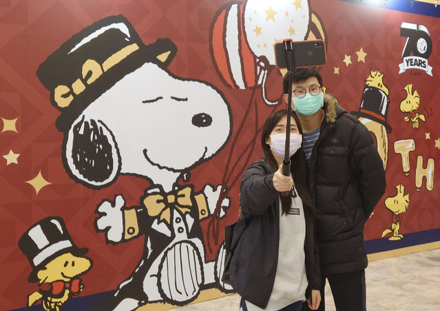 People wearing face masks to help curb the spread of the coronavirus visit the popular cartoon dog Snoopy's 70th Anniversary Exhibition in Taipei, Taiwan, Saturday, February 20, 2021. (Photo by Chiang Ying-ying/AP Photo)