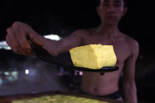 A worker holds a boiled tofu in a traditional tofu factory in Depok, Indonesia, 21 January 2015. (Photo by Adi Weda/EPA)