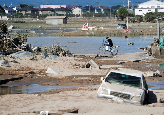 A local resident is seen in a flooded area in Mabi town in Kurashiki, Okayama Prefecture, Japan, July 9, 2018. (Photo by Issei Kato/Reuters)