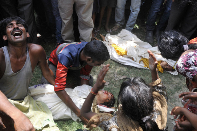 Grief-stricken family members react over the bodies of their children who died after consuming a free mid day meal at a school at Gandaman in Saran District, India's Bihar state, on July 17, 2013. Twenty-two children have died after eating a free lunch feared to contain poisonous chemicals at an Indian primary school, officials said, as the tragedy sparked angry street protests. (Photo by AFP Photo)
