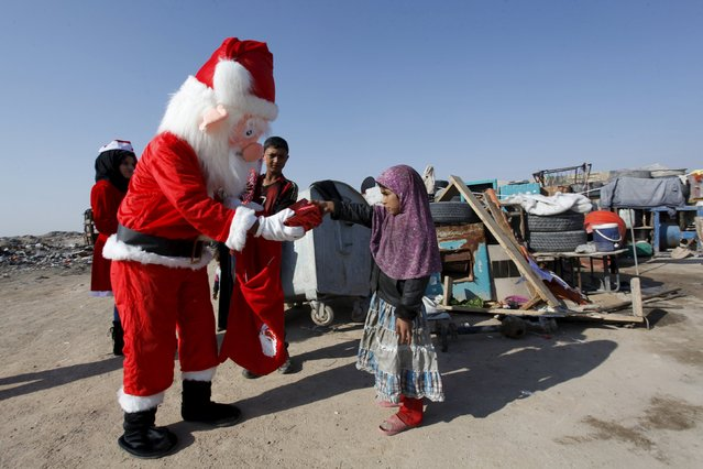 A volunteer wearing a Santa Claus costume distributes presents to children at a poor community in Najaf, south of Baghdad, December 19, 2015. (Photo by Alaa Al-Marjani/Reuters)