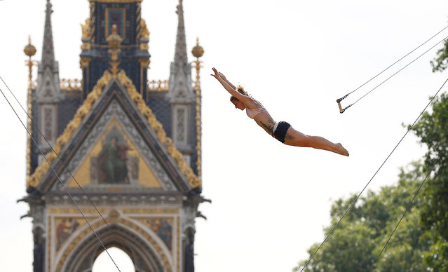 A trapeze artist practices her routine near to the Albert Memorial in Hyde Park, in London, Britain July 21, 2018. (Photo by Peter Nicholls/Reuters)