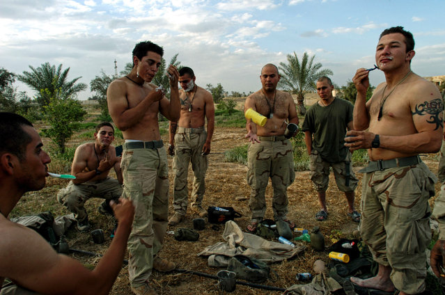 United States Marines take a break to shave in front of one of Saddam Hussain's presidential palaces the day Tikrit fell from Republican Guard rule in Iraq, April 15, 2003.  (Photo by Lynsey Addario/Corbis)