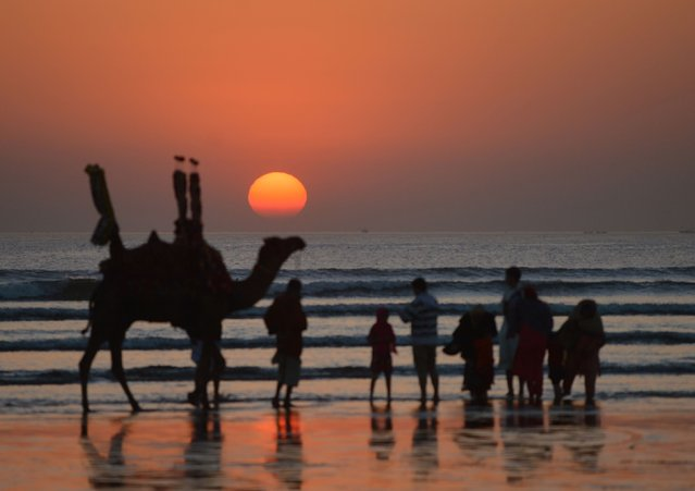 Silhouetted Pakistani look at a sun set on a beach on the shortest day of the year in Karachi, Pakistan on December 22, 2017. (Photo by Rizwan Tabassum/AFP Photo)