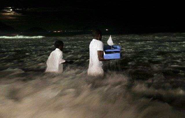 Followers of the Afro-Brazilian religion Umbanda carry offerings for Iemanja, goddess of the sea, at Copacabana Beach in Rio de Janeiro December 27, 2015. (Photo by Lunae Parracho/Reuters)