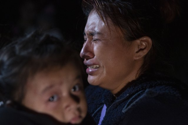 A woman from Guatemala weeps as she carries her child after being smuggled across the Rio Grande river in Roma, Texas Tuesday, March 30, 2021. Roma, a town of 10,000 people with historic buildings and boarded-up storefronts in Texas' Rio Grande Valley, is the latest epicenter of illegal crossings, where growing numbers of families and children are entering the United States to seek asylum. (Photo by Dario Lopez-Mills/AP Photo)