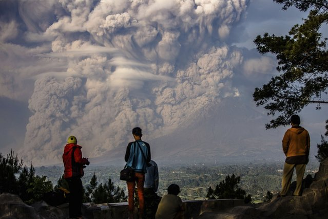 People watch as Mt. Sinabung ejects ash into the air during an eruption in Karo regency, Indonesia's North Sumatra province February 9, 2015  in this photo taken by Antara Foto. (Photo by Endro Lewa/Reuters/Antara Foto)