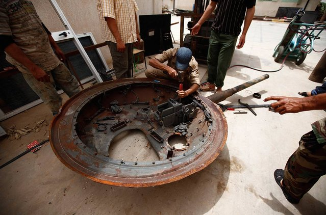 A Libyan man tries to remove a cannon from a part of a tank, belonging to forces loyal to Libyan leader Muammar el-Qaddafi, with plans to reuse it, in the western Libyan city of Misurata, on June 7, 2013. (Photo by Zohra Bensemra/Reuters)