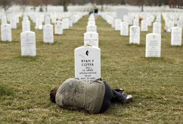 Lesleigh Coyer, 25, of Saginaw, Michigan, lies down in front of the grave of her brother, Ryan Coyer, who served with the U.S. Army in both Iraq and Afghanistan, at Arlington National Cemetery in Virginia in this March 11, 2013 file photo. Coyer died of complications from an injury sustained in Afghanistan. (Photo by Kevin Lamarque/Reuters)