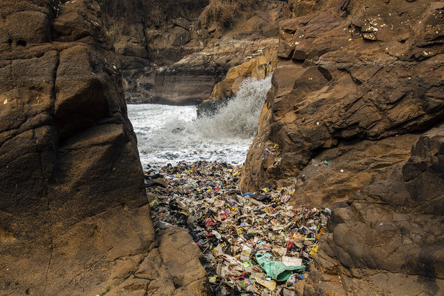 Water dirtied by factory waste plunges through a natural rock formation cluttered with some of the thousands of tons of plastic waste dumped into the Citarum river on August 27, 2018 outside Bandung, Java, Indonesia. (Photo by Ed Wray/Getty Images)