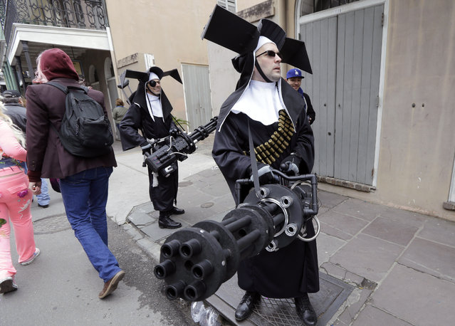 """Revelers dressed as the """"Sisters Of No Mercy"""" walk throughout the French Quarter on Mardi Gras in New Orleans, Tuesday, February 17, 2015. Revelers in glitzy costumes filled the streets of New Orleans for the annual fat Tuesday bash, opening a day of partying, parades and good-natured jostling for beads and trinkets tossed from passing floats. (Photo by Gerald Herbert/AP Photo)"""