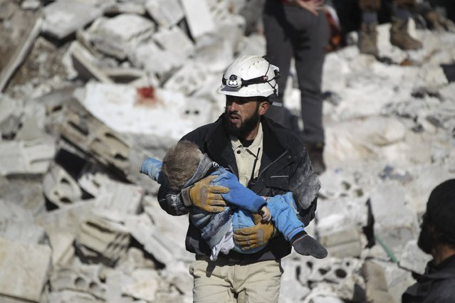A civil defence member carries a dead child in a site hit by what activists said were airstrikes carried out by the Russian air force in the rebel-controlled area of Maaret al-Numan town in Idlib province, Syria January 9, 2016. (Photo by Khalil Ashawi/Reuters)
