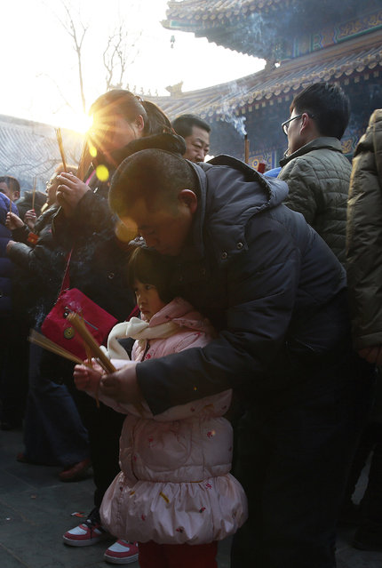 A man shows his child the way to offer prayers on the first day of the Chinese Lunar New Year at Yonghegong Lama Temple in Beijing, China Thursday, February 19, 2015. (Photo by Andy Wong/AP Photo)