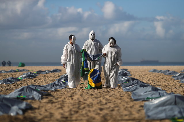 Activists from NGO Rio de Paz carry a Brazilian flag as they display hundreds of plastic bags, representing dead bodies, during a protest against Jair Bolsonaro's COVID-19 policies, amid the coronavirus disease (COVID-19) outbreak, in Copacabana beach, in Rio de Janeiro, Brazil, April 30, 2021. (Photo by Pilar Olivares/Reuters)