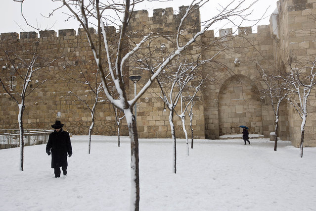 An ultra-Orthodox Jewish man walks in the snow near the Jaffa gate in Jerusalem's Old City, Friday,February 20, 2015. (Photo by Sebastian Scheiner/AP Photo)