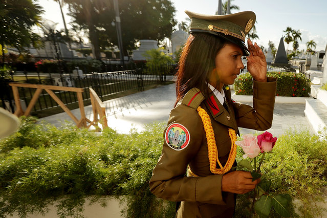 A military guard carries flowers through the Cementerio Santa Ifigenia where the remains of former Cuban President Fidel Castro were entombed December 4, 2016 in Santiago de Cuba, Cuba. The tomb stands to the side of a memorial to the rebel soldiers killed in an attack that Castro led on Santiago's Moncada barracks on July 26, 1953, and in front of the mausoleum of Cuban national hero Jose Marti. (Photo by Chip Somodevilla/Getty Images)