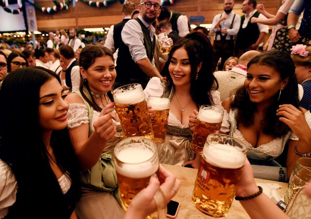 Visitors cheer with beers during the opening day of the 185th Oktoberfest in Munich, Germany September 22, 2018. (Photo by Andreas Gebert/Reuters)
