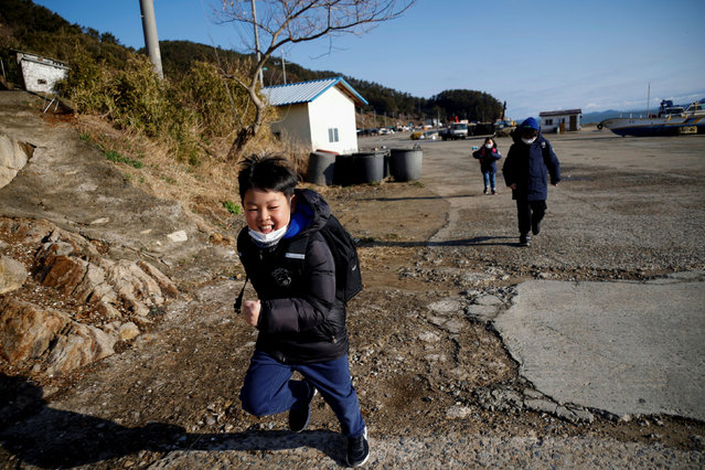 Lyoo Chan-hee, 10, Lyoo Chae-hee, 7, and Kim Si-hu, 9, make their way to school on the first day of the new semester, on Nokdo island in Boryeong, South Korea, March 2, 2021. Lyoo Chan-hee wishes he wasn't one of the last three schoolkids left playing on the beaches of Nokdo island. Instead, he often plays with Kim Si-young - aged 66, and one of the last 100 or so residents of a once-vibrant fishing village emblematic of the demographic crisis unfolding in South Korea. (Photo by Kim Hong-Ji/Reuters)