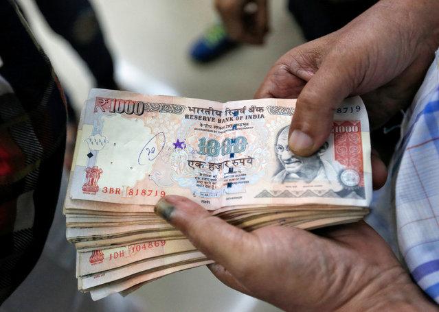 A customer waits to deposit 1000 Indian rupee banknotes in a cash deposit machine at bank in Mumbai, India, November 8, 2016. (Photo by Danish Siddiqui/Reuters)