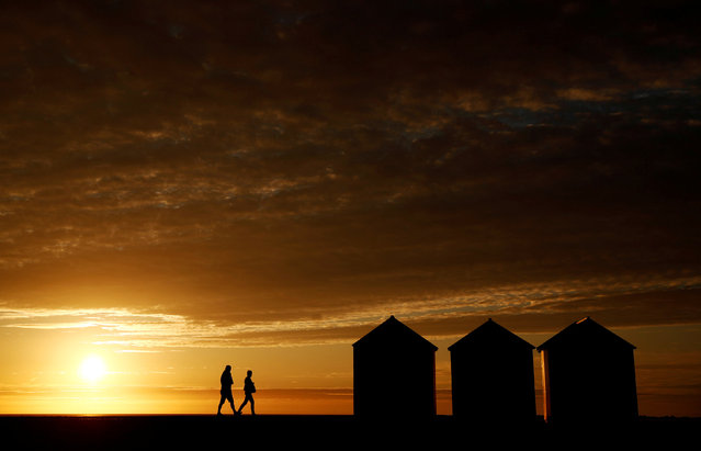 People enjoy a walk at sunset past beach cabins on the pebbled beach in Cayeux-sur-Mer, on the North coast of France, September 9, 2018. (Photo by Christian Hartmann/Reuters)