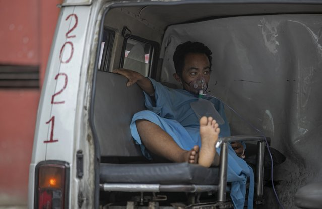 A COVID-19 patient receives oxygen in an ambulance outside an emergency ward of a hospital as he waits for an intensive care bed to be allotted in Kathmandu, Nepal, Friday, May 7, 2021. (Photo by Niranjan Shrestha/AP Photo)