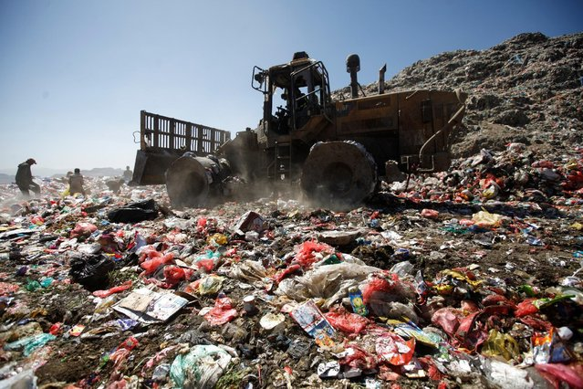 A bulldozer moves piles of rubbish at a landfill site on the outskirts of Sanaa, Yemen November 16, 2016. (Photo by Mohamed al-Sayaghi/Reuters)