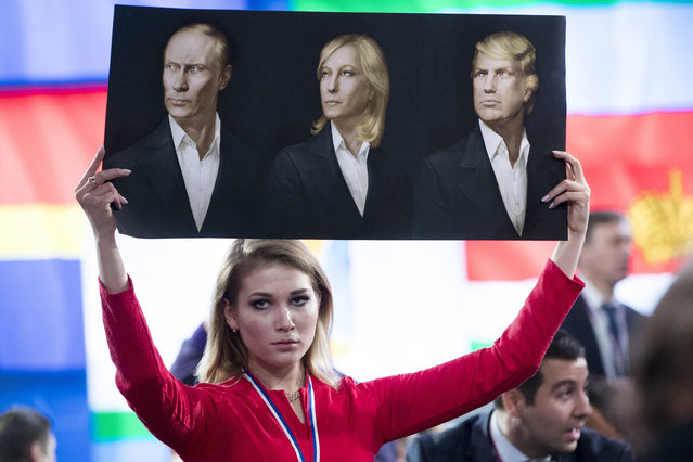 Pro-Putin activist Maria Katasonova holds a poster with portraits of Russian President Vladimir Putin, left, France's far-right National Front president Marine Le Pen, center, and President-elect Donald Trump prior to Russian President's annual news conference in Moscow, Russia, Friday, December 23, 2016. (Photo by Pavel Golovkin/AP Photo)