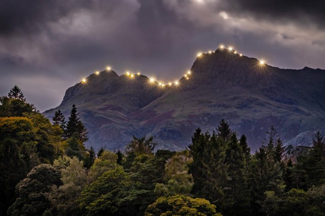 The Langdale Pikes in the Lake District in North West England are illuminated on September 14, 2020 by a team of 30 climbers to celebrate the 50th anniversary of the local mountain rescue service. (Photo by Tom Mcnally/Triangle News)