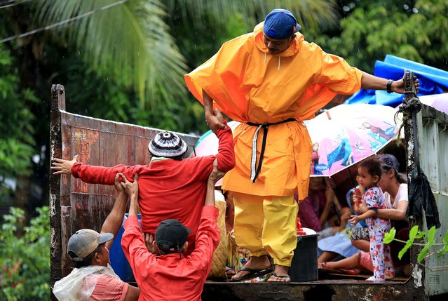 Residents are assisted into a truck after the local government implemented preemptive evacuations at Barangay Matnog, Daraga, Albay province on December 25, 2016, due to the approaching typhoon Nock-Ten. (Photo by AFP Photo)