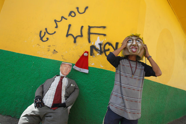 A man puts a mask depicting  U.S. President-elect Donald Trump on an effigy that will be burnt during a local New Year's Eve celebration, at La Leona neighborhood in Tegucigalpa, Honduras, December 27, 2016. (Photo by Jorge Cabrera/Reuters)