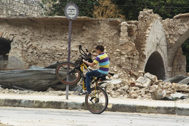 A boy rides a bicycle past damaged buildings along a street in a rebel-controlled area of Aleppo, Syria, August 30, 2015. (Photo by Abdalrhman Ismail/Reuters)