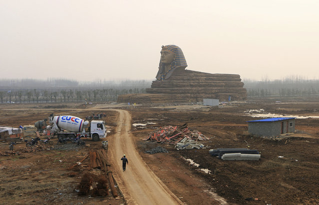 A worker walks on a dirt road next to a full scale replica of the sphinx, which is part of an unfinished movie and animation tourism theme park, in Chuzhou, Anhui province, March 3, 2015. (Photo by Reuters/Stringer)
