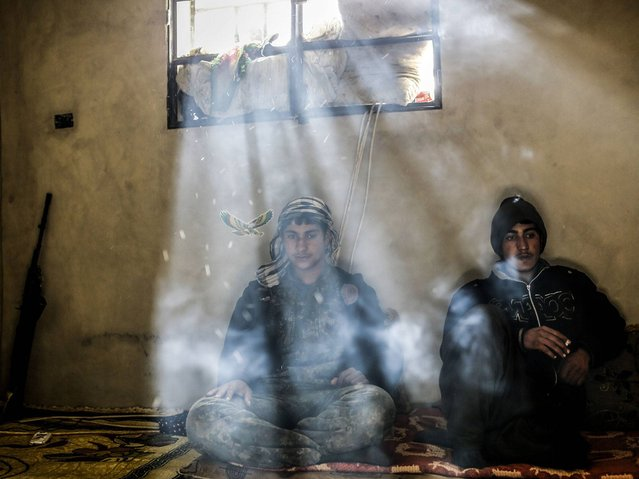 Kurdish fighters rest in a house on the outskirts of the Syrian town of Kobane, also known as Ain al-Arab, on March 30, 2015. (Photo by Yasin Akgul/AFP Photo)