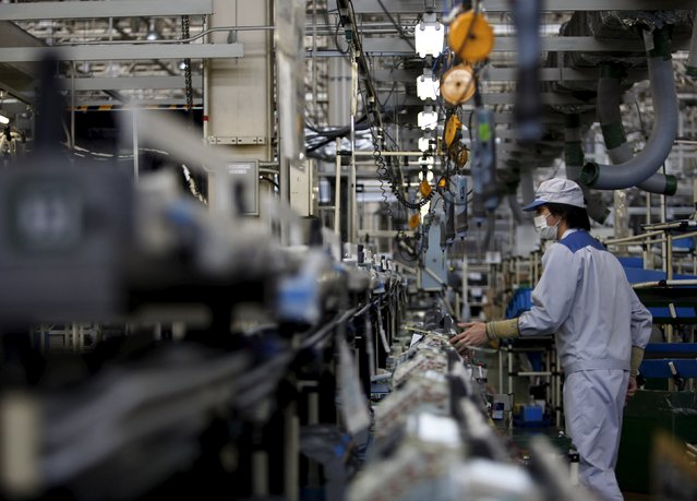A Daikin Industries Ltd employee inspects indoor air conditioning units at the production line at the company's Kusatsu factory in Shiga prefecture, western Japan March 20, 2015. (Photo by Yuya Shino/Reuters)