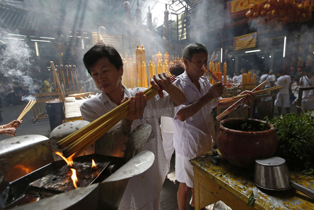 In this October 8, 2018, photo,  a woman lights long incense sticks at a Chinese temple in Bangkok, Thailand, to mark the eve of the Vegetarian Festival. During the festival that runs from Oct. 9 to 17 in 2018, worshippers refrain from eating animal products over the nine days to coincide with the celebration of the nine Chinese Emperor Gods. (Photo by Sakchai Lalit/AP Photo)