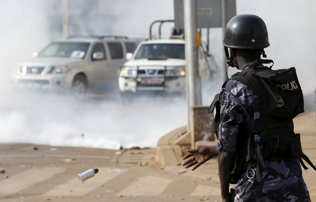 A riot police officer throws a tear gas canister as police and military forces disperse a procession by Uganda's leading opposition party Forum for Democratic Change supporters with their presidential candidate to a campaign ground, in Kampala, Uganda, February 15, 2016. (Photo by James Akena/Reuters)