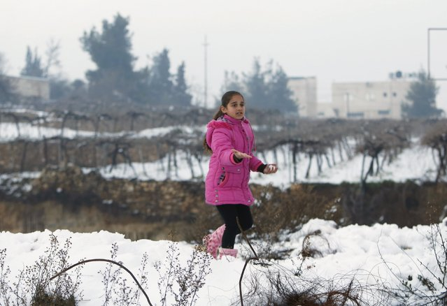 A Palestinian girl gestures as she plays with snow during a snowstorm in the West Bank town of Halhul, north of Hebron January 27, 2016. (Photo by Mussa Qawasma/Reuters)