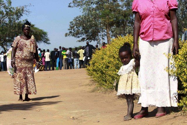 A mother leaves with her child after casting her ballot at a polling station during the presidential elections in Kirihura in western Uganda, February 18, 2016. (Photo by James Akena/Reuters)