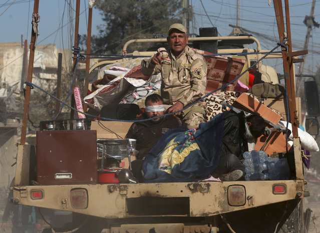 Iraqi security forces detain a suspected Islamic State fighter during a military operation on the eastern side of Mosul, Iraq, Thursday, January 12, 2017. (Photo by Khalid Mohammed/AP Photo)