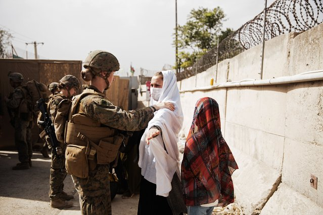 In this photo provided by the U.S. Marine Corps, two civilians during processing through an Evacuee Control Checkpoint during an evacuation at Hamid Karzai International Airport, in Kabul, Afghanistan, Wednesday, August 18, 2021. (Photo by Staff Sgt. Victor Mancilla/U.S. Marine Corps via AP Photo)