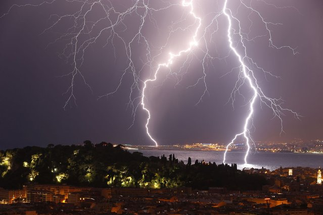 """Flashes of lightning strike above the """"Baie des Anges"""", on October 4, 2013, in Nice, southeastern France. (Photo by Valery Hache/AFP Photo)"""