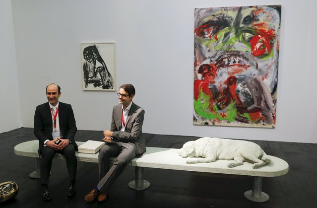 Gallerists sit on a concrete bench showing a sleeping dog by Italian artist Alberto Garutti at the Art Cologne 2015 fair in Cologne April 15, 2015. The bench is part of a contemporary art project of the little Italian municipality of Trivero, northeast of Turin in the Piedmont region, portraying dogs that belong to Trivero families. (Photo by Wolfgang Rattay/Reuters)