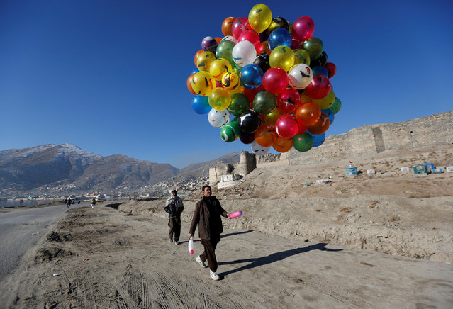 An Afghan man holds balloons for sale in Kabul, Afghanistan January 8, 2017. (Photo by Mohammad Ismail/Reuters)