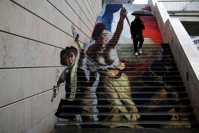"A man passes by an unfinished street art graffiti made in a stairway by French street artists Zag and Sia in Paris on March 1, 2016. The two artists drew inspiration from famous ""Liberty Leading the People"" (La Liberte guidant le peuple) painting by French Eugene Delacroix commemorating the July Revolution of 1830 and viewed as a symbol of the French Republic. (Photo by Joel Saget/AFP Photo)"