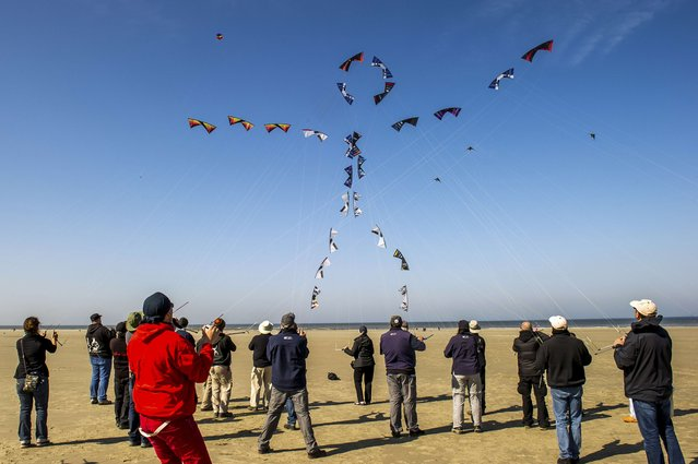 "People fly their kites to form the shape of a stick figure in the sky on the beach in Berck, northern France, on April 20, 2015, during the 29th ""Rencontres Internationales de Cerfs Volants"" (International Kite Meeting) which runs from April 18 to 26. (Photo by Philippe Huguen/AFP Photo)"