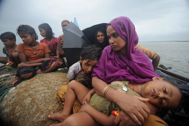 Rohingya Muslims, trying to cross the Naf river into Bangladesh to escape sectarian violence in Myanmar, look on from an intercepted boat in Teknaf on June 13, 2012. (Photo by Munir Uz Zaman/AFP Photo)