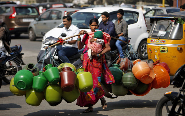 An Indian woman vendor carries plastic containers for sale as she walks on a street in Hyderabad, India, Friday, January 24, 2014. One plastic container sells at approximately one US dollar and the woman manages to earn about 2-3 dollars a day. (Photo by Mahesh Kumar A./AP Photo)