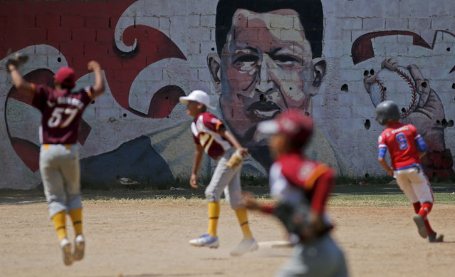 Youths play baseball at a field decorated with a mural of Venezuela's late President Hugo Chavez in Caracas, Venezuela, Tuesday, March 5, 2019. On Tuesday, which marks six years after his death from cancer, Chavez continues to unleash mixed feelings among Venezuelans: some remember him as the father of a revolution that defended the poor, while others blame him for the deep and prolonged crisis that overwhelms the South American country. (Photo by Eduardo Verdugo/AP Photo)