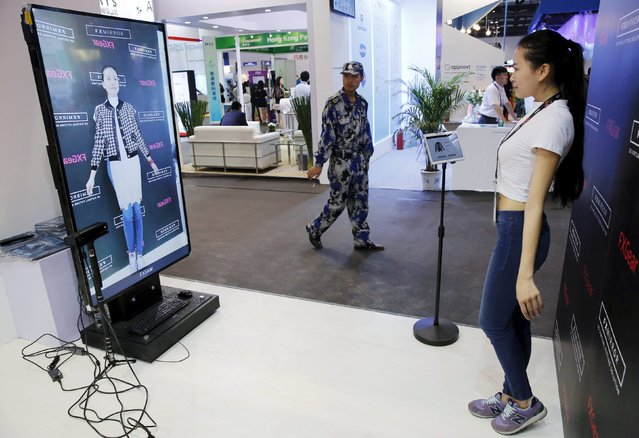 A staff demonstrates FXMirror, a virtual reality fitting room solution developed by FXGear, at the Global Mobile Internet Conference (GMIC) 2015 in Beijing, China, April 28, 2015. (Photo by Kim Kyung-Hoon/Reuters)