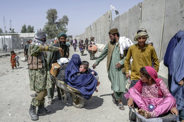 People with their belongings rush to pass to Pakistan from the Afghanistan border in Spin Boldak on September 25, 2021. (Photo by Bulent Kilic/AFP Photo)